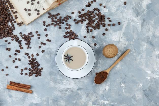 灰色の漆喰の背景の上のカップにクッキー、コーヒー豆、挽いたコーヒー、本、スパイス、コーヒーのセットです。上面図。