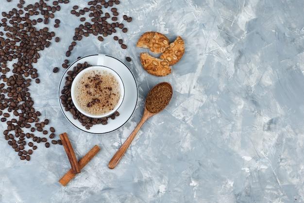 Набор печенья, кофейных зерен, молотого кофе, палочек корицы и кофе в чашке на сером гипсовом фоне. вид сверху.