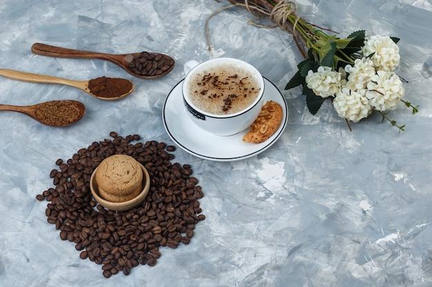 汚れた灰色の背景にクッキー、コーヒー豆、挽いたコーヒー、花、カップのコーヒーのセットです。ハイアングルビュー。