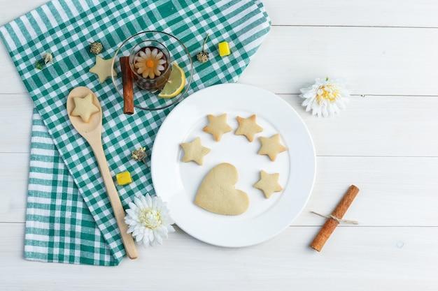 Набор печенья, лимона, палочки корицы, кубиков сахара, цветов и чая в стакане на фоне деревянных и кухонных полотенец. вид сверху.