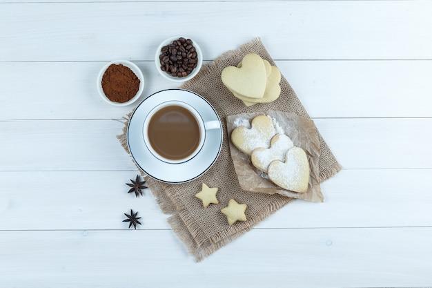 Набор печенья, специй, кофейных зерен, молотого кофе и кофе в чашке на деревянном фоне и кусок мешка. вид сверху.