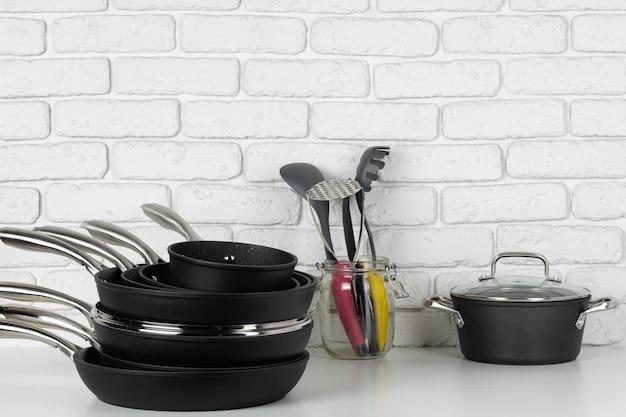 白いレンガの壁に対してテーブルの上の調理器具のセット