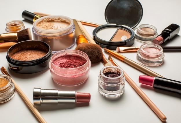 化粧ブラシ、ブロンザー、ミネラルルースパウダー、白い背景の上の口紅のセット
