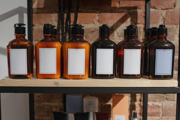 木製の棚の上の化粧品の暗い琥珀色のガラス瓶のセット。モックアップ