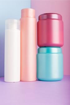 ピンクの壁に化粧品のセット。シャンプー、マスク、コンディショナー、シャワージェルの化粧品パッケージコレクション。ピンク、白、青のペットボトル、化粧箱