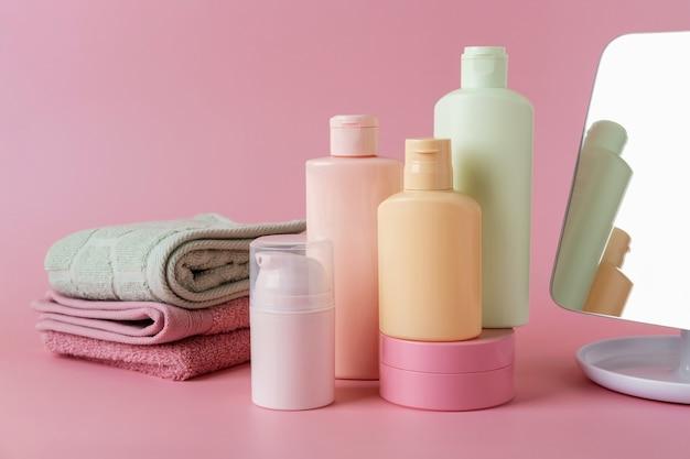 ピンクの背景に化粧品スキンケア製品、フェイシャル製品、スキンケアブランクボトルパッケージのセット。美容とスパのコンセプト。