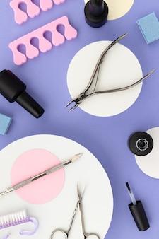Набор косметических инструментов для маникюра и педикюра на фиолетовом фоне. шаблон креативной композиции для салона красоты