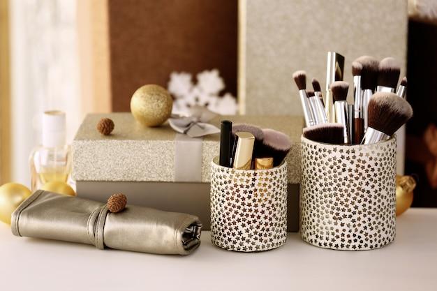 Набор косметики и коробка с подарком на белом столе на размытом фоне
