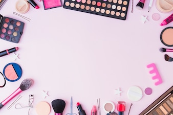 Set of cosmetics products forming frame on pink background