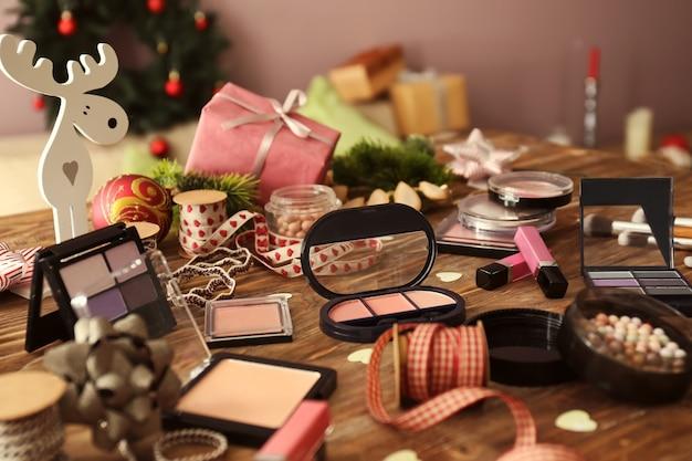 木製のテーブルの上のクリスマスプレゼントの装飾と化粧品のセット