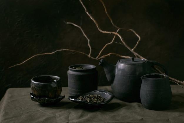 クラフト手作りセラミックティーポットと暗い背景のカップのセット