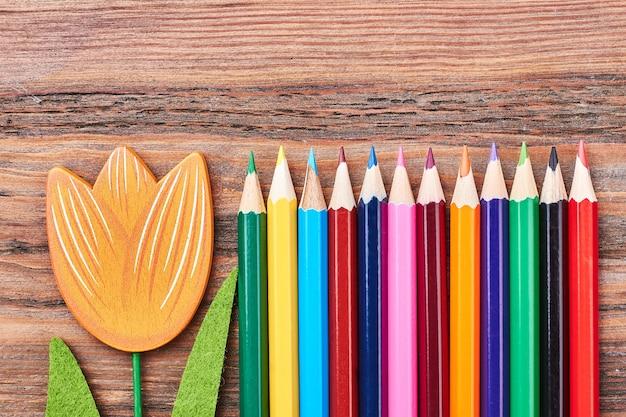 Набор цветных мелков и цветов. творческая композиция на деревянной поверхности.