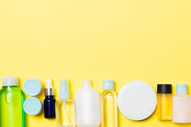 黄色の表面にクリームと化粧品のボトルと瓶のセット