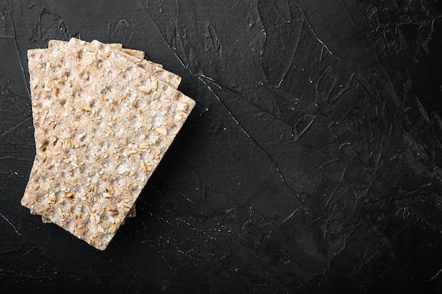 검은색 돌 테이블 배경에 있는 바삭한 빵 세트, 텍스트 복사 공간이 있는 평면도