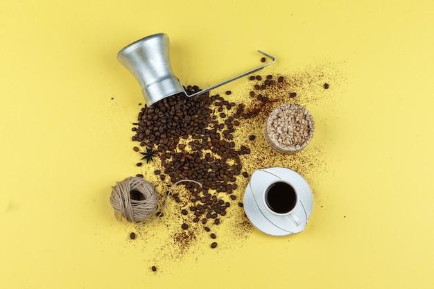 黄色の背景の水差しにコーヒー、お餅、ロープ、コーヒー豆のセット。フラットレイ。