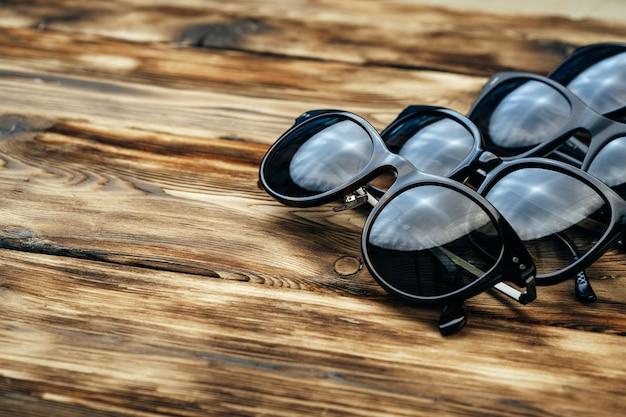 Набор темных солнцезащитных очков на коричневой деревянной поверхности