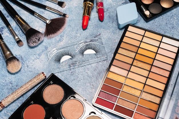 Набор декоративной косметики, кисти для макияжа накладные ресницы на синем фоне. вид сверху