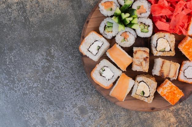 Набор вкусных различных суши на деревянной тарелке