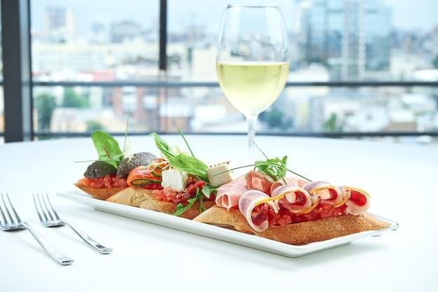 Набор вкусных итальянских брускетт с ветчиной, ветчиной, помидорами, сыром из лосося, подается с бокалом вина с видом на город.