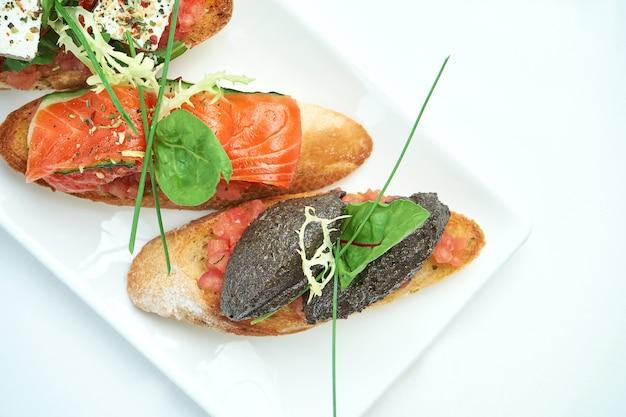 Набор вкусных итальянских брускетт с ветчиной, ветчиной, помидорами, сыром из лосося, подается с бокалом вина