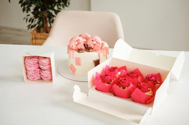 バースデーケーキのカップケーキとマシュマロを食欲をそそる白いテーブルの上のおいしいピンクのデザートのセット