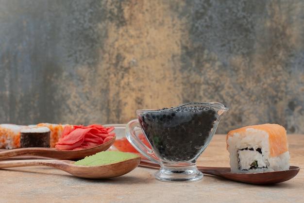 Набор вкусных суши-роллов с ложкой и соевым соусом на мраморной поверхности