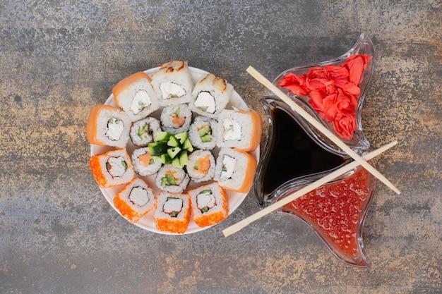 Набор вкусных суши с палочками для еды и имбирем на мраморной поверхности