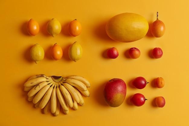 소비를위한 맛있는 열대 과일 세트. 레몬, cumquat, 복숭아, 타마 릴로, 바나나, 멜론 노란색 배경. 과일 샐러드 재료로 사용되는 비타민이 풍부한 영양 작물