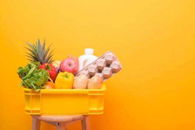 黄色のプラスチックの箱で生の食品のセット