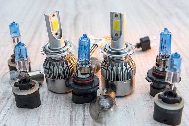 白い木製の背景にヘッドライトを修理するための別の自動ランプのセットです。現代の電球。
