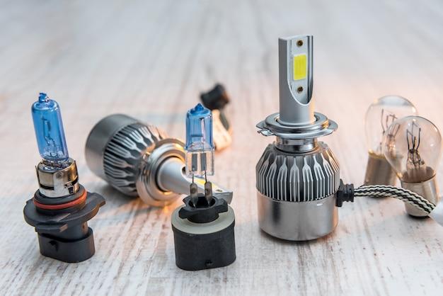 白い木製のテーブルのヘッドライトを修理するための別の自動ランプのセット。現代の電球。