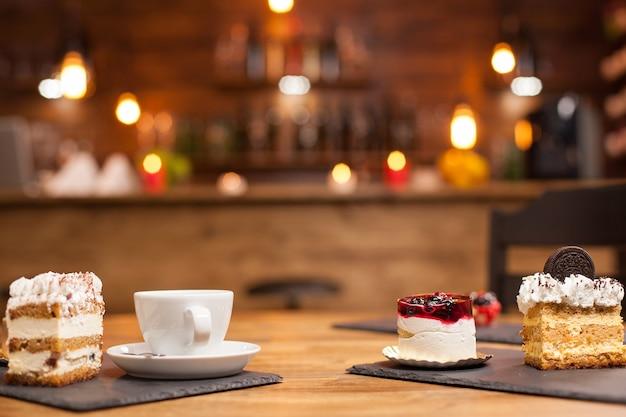 木製のテーブルに並べて焼きたてのさまざまなケーキやデザートのセット。天然フルーツをのせた美味しいケーキ。おいしいコーヒーのカップ。上にビスケットを載せたケーキのスライス。