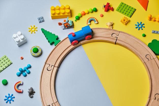 さまざまな子供のおもちゃのセット、木製のレール、電車、コンストラクターで作られた黄色と青の背景にテキスト用のコピースペースがあります。上面図、フラットレイ。