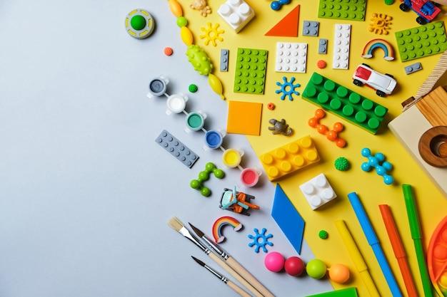 さまざまな子供のおもちゃ、木製の鉄道、電車、コンストラクターのセット。黄色と青の背景にテキスト用のコピースペースがあります。上面図、フラットレイ。