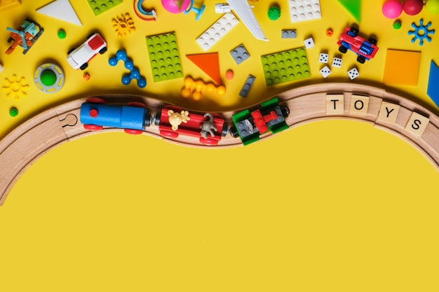 さまざまな子供のおもちゃ、木製の鉄道、電車、テキストのコピースペースと黄色の背景のコンストラクターのセット。上面図、フラットレイ。