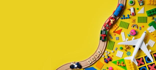 Набор различных детских игрушек, деревянная железная дорога, поезд, конструктор на желтой поверхности
