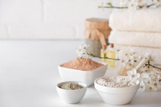 흰색 표면에 다른 화장품 점토 진흙 가루의 집합입니다. 수제 페이셜 및 바디 마스크 또는 스크럽 및 꽃 체리의 신선한 장식 재료. 스파 및 푸터 바 브 개념입니다.