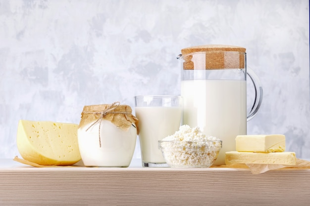 Набор различных молочных продуктов на деревянном столе.