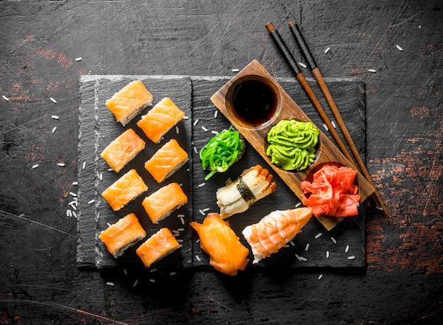Набор различных видов суши-роллов с лососем. на темном деревенском