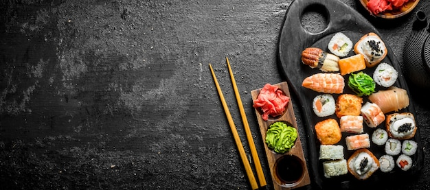 Набор различных видов суши-роллов с лососем, креветками и овощами. на черном деревенском