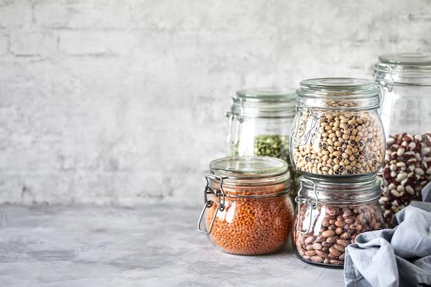 Набор различных бобовых в стеклянных банках, бетонный белый стол. источник белка для вегетарианцев. концепция здорового питания и хранения продуктов питания.