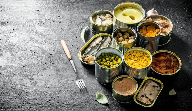 缶詰食品とさまざまなオープンブリキ缶のセット。黒の素朴な背景に