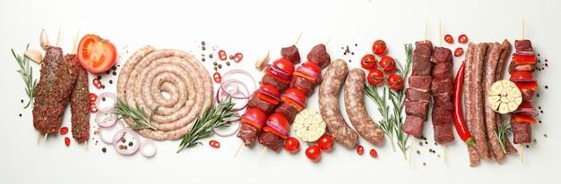 Набор различного сырого мяса барбекю на белом столе, вид сверху