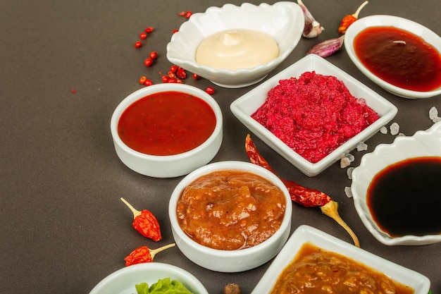 Набор различных соусов - кетчуп, майонез, шашлык, соя, чатни, васаби, аджика, хрен, айоли, маринара. темный каменный бетонный фон, крупным планом