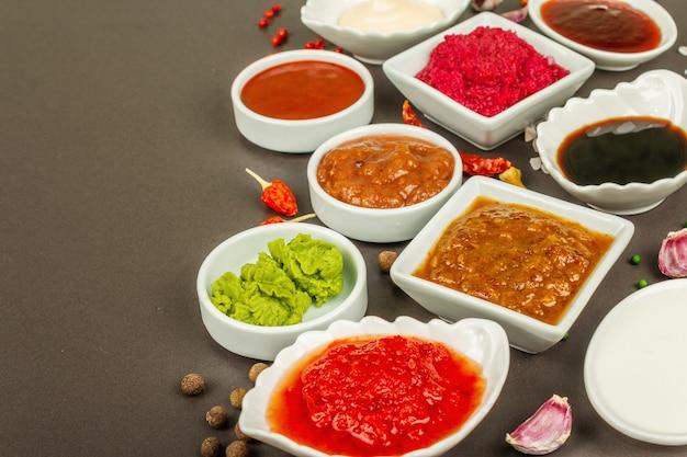 Набор различных соусов - кетчуп, майонез, шашлык, соя, чатни, васаби, аджика, хрен, айоли, маринара. темный каменный бетонный фон, копия пространства