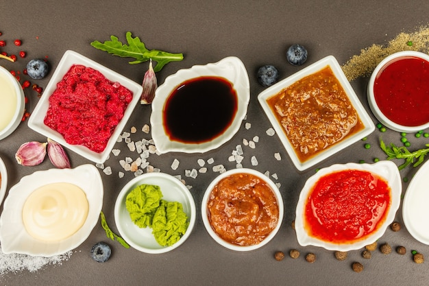 Набор различных соусов - кетчуп, майонез, шашлык, соя, чатни, васаби, аджика, хрен, айоли, маринара. темный каменный бетонный фон, вид сверху