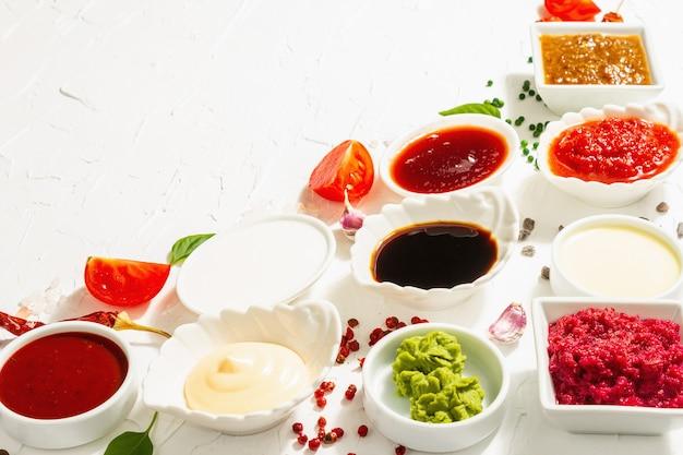 Набор различных соусов - кетчуп, майонез, шашлык, соя, чатни, васаби, аджика, хрен, айоли, маринара. модный жесткий свет, темная тень. белый фон шпатлевки, крупным планом