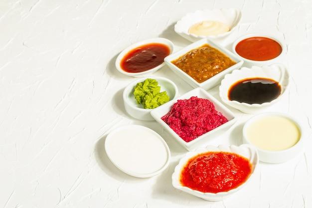 Набор различных соусов - кетчуп, майонез, шашлык, соя, чатни, васаби, аджика, хрен, айоли, маринара. модный жесткий свет, темная тень. белый фон шпатлевки, копия пространства