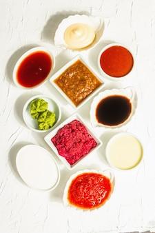 Набор различных соусов - кетчуп, майонез, шашлык, соя, чатни, васаби, аджика, хрен, айоли, маринара. модный жесткий свет, темная тень. белый фон шпатлевки, вид сверху