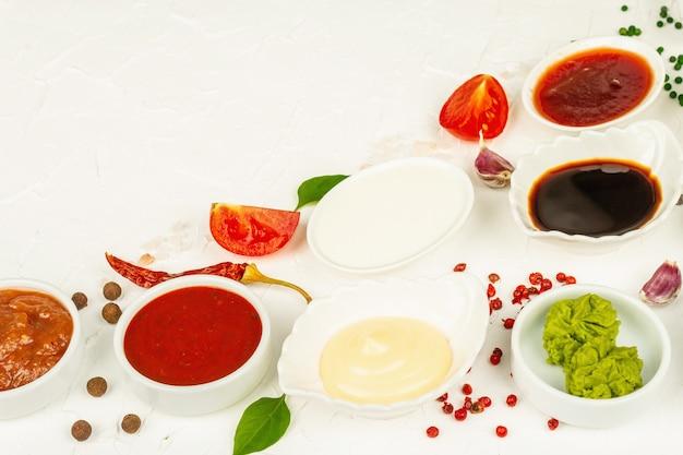 Набор различных соусов - кетчуп, майонез, шашлык, соя, чатни, васаби, аджика, хрен, айоли, маринара. белый фон шпатлевки, копия пространства